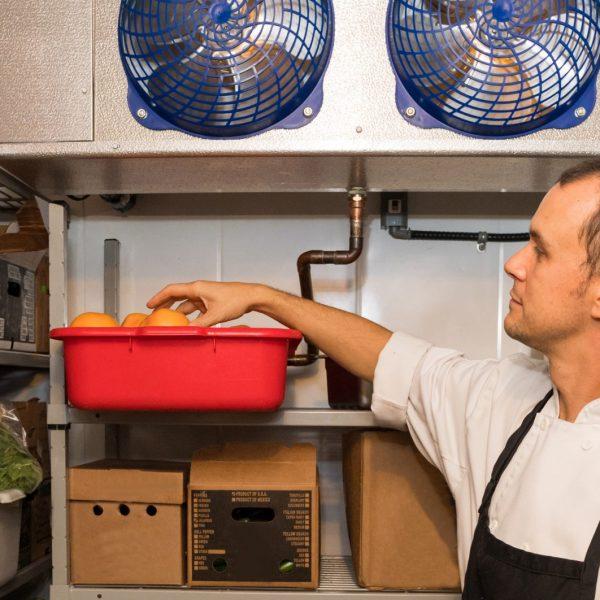 man inside a walk in refrigerator selecting ingredients