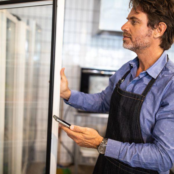 man reaching into a reach in refrigerator, wishing it was a walk in refrigerator
