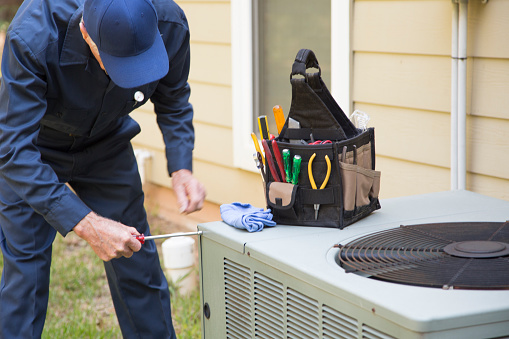 man fixing an air conditioner at a pittsburgh home as part of our residential hvac
