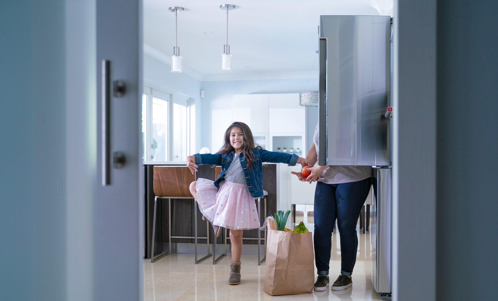residential refrigerator with a young girl and her mom filling it with groceries