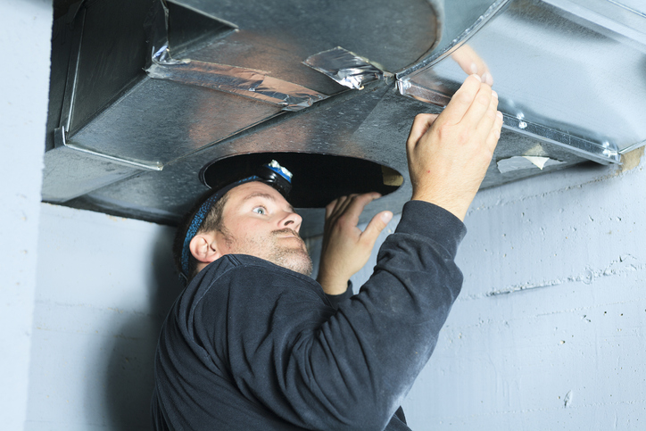 serviceman working on a heating duct in a Pittsburgh residence as a part of  an hvac service call